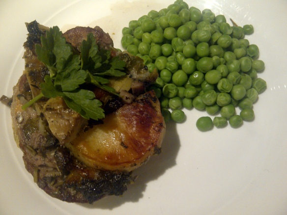 Image of a portion of spring lamb hotpot served on a white plate with peas