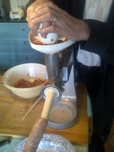 Image of sausage meat being fed into sausage-making attachment on a food processor