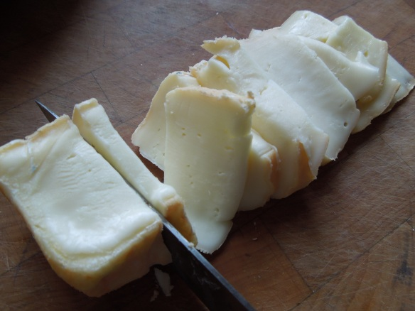 Image of taleggio cheese being sliced thinly