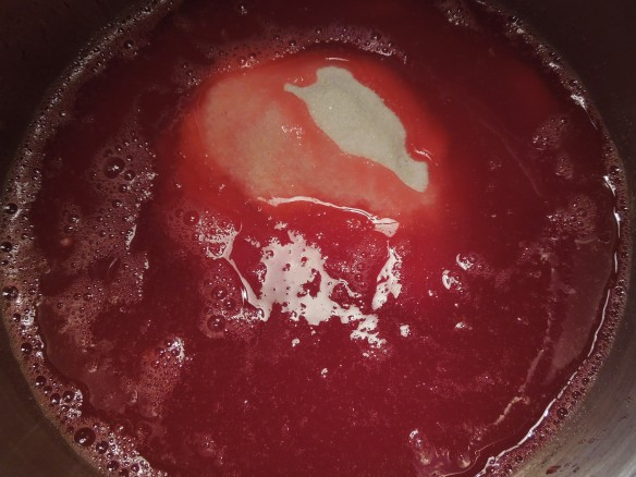 Image of sugar poured into a pan of redcurrant juice