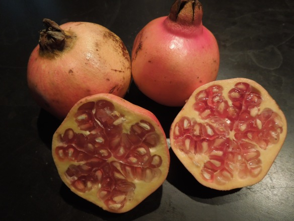 Image of pomegranates, whole and sliced
