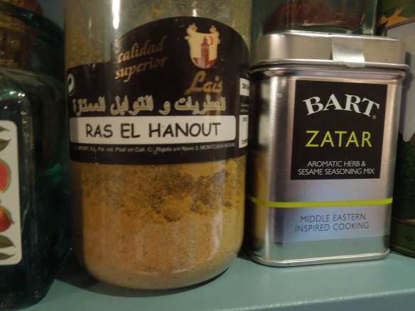 Image of jar of ras el hanout on a spice shelf