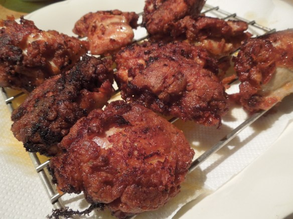 Image of fried chicken draining on rack