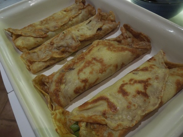 Image of stuffed and rolled pancakes in baking dish