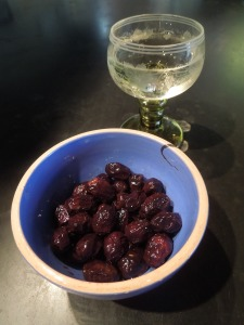 Image of olives in a bowl and a glass of wine