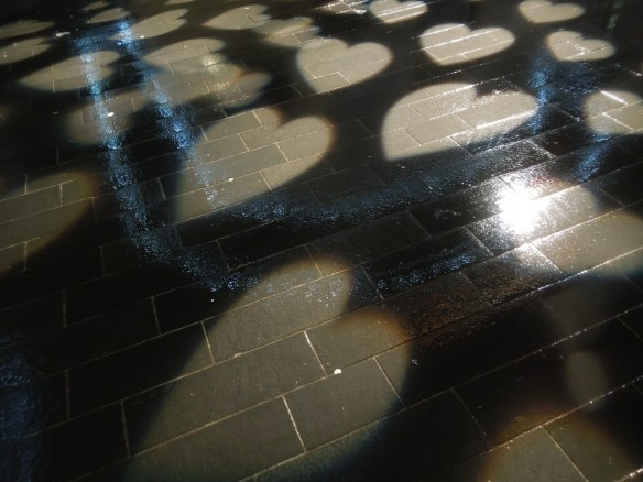Image of hearts projected onto a wet pavement