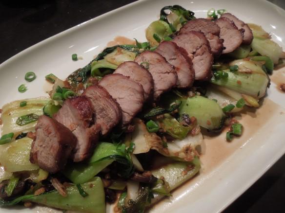 Image of pork served over wilted veg