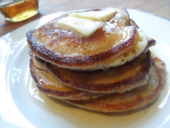 Image of a stack of American pancakes drizzled with maple syrup and melted butter