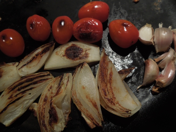 Image of onion, tomato and garlic being blackened in a pan