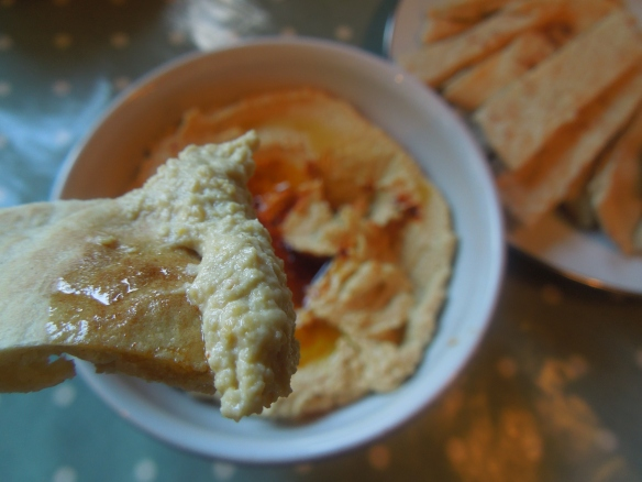 Image of pitta dunked in hummus