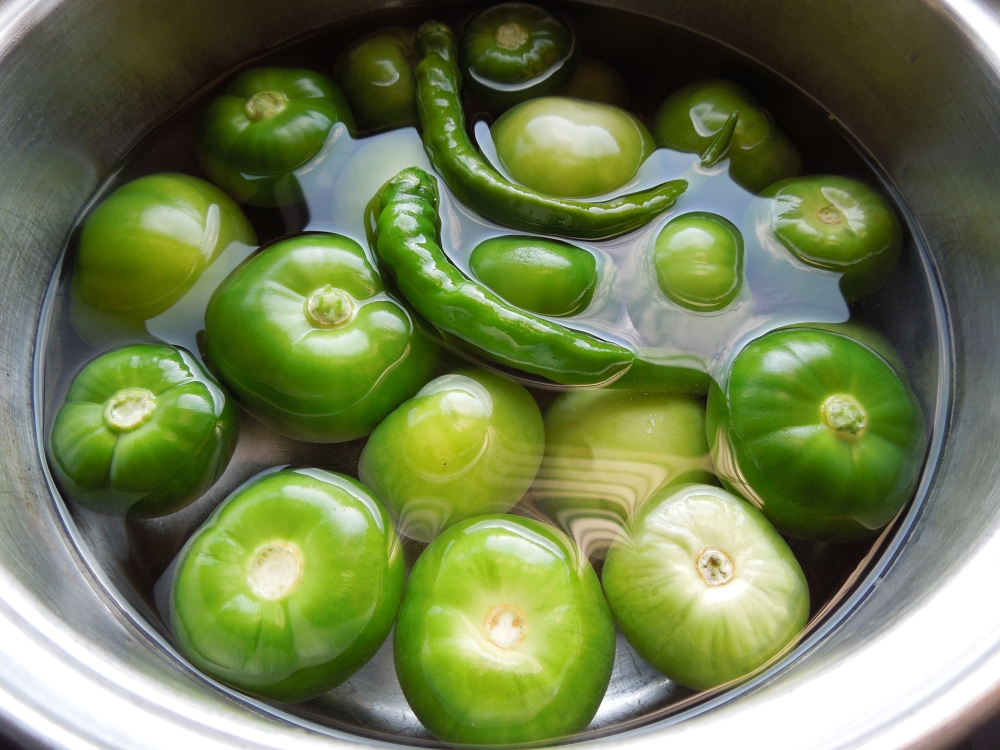 Image of tomatillos in cooking pot with chillies