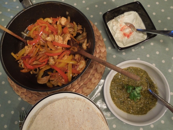 Image of fajita filling, tomatillo salsa, yorghurt suace and tortillas on the table