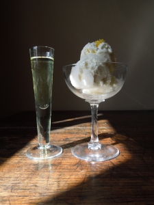 Image of a shot glass of limoncello alongside lemon yoghurt ice cream