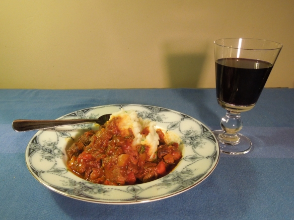 Image of a serving of stew with glass of wine