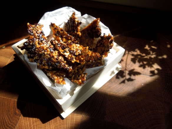 Image of shards of cocoa nib and hazelnut croquant in a box