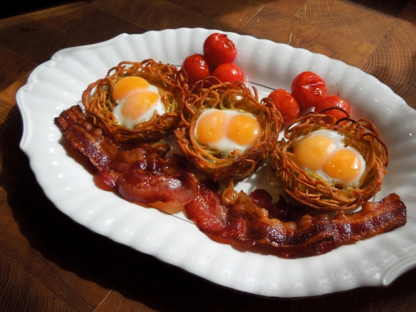 Image of eggs in potato nests with bacon and tomatoes