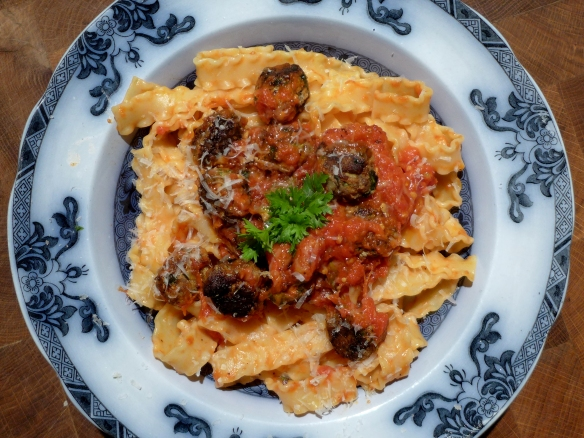 Image of cheatballs with tomato sauce, served over pasta