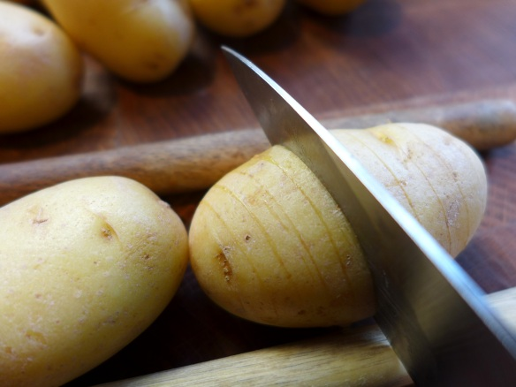 Image of potatoes being sliced between spoon handles