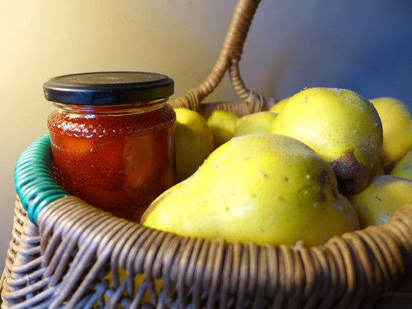 Image of a jar of quince conserve in a basket of fresh quinces