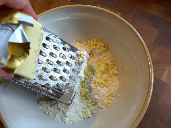 Image of butter being grated into flour